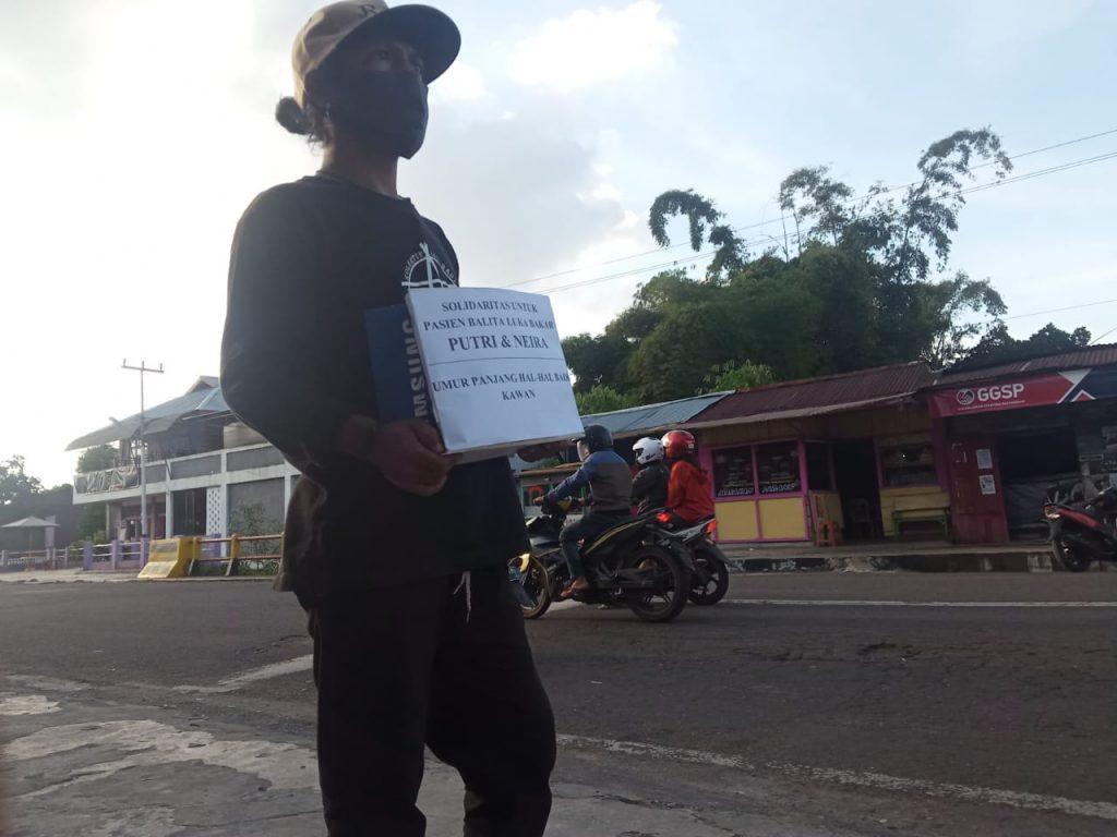 Seorang pemuda sedang melakukan penggalangan dana untuk biaya Rumah Sakit dua bocah pasien luka bakar asal Manggarai Barat. Foto: Istimewa